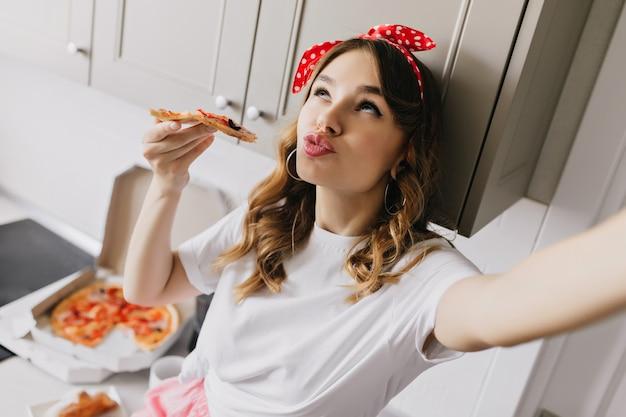 Romantisches weißes mädchen, das selfie beim essen der pizza macht. innenaufnahme der lockigen kaukasischen dame, die während des frühstücks herumalbert.