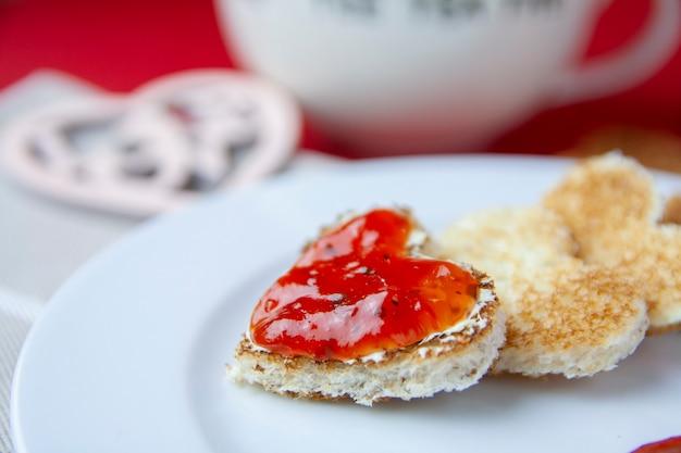 Romatischer herzförmiger toast mit marmelade und tee