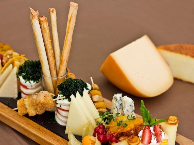 Roquefort mit blauem schimmel, cheddar, geräuchertem käse, mozzarella auf einem holzbrett.