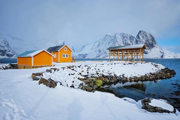 Rorbu-haus und trocknende flocken für stockfisch-kabeljau im winter. lofoten, norwegen