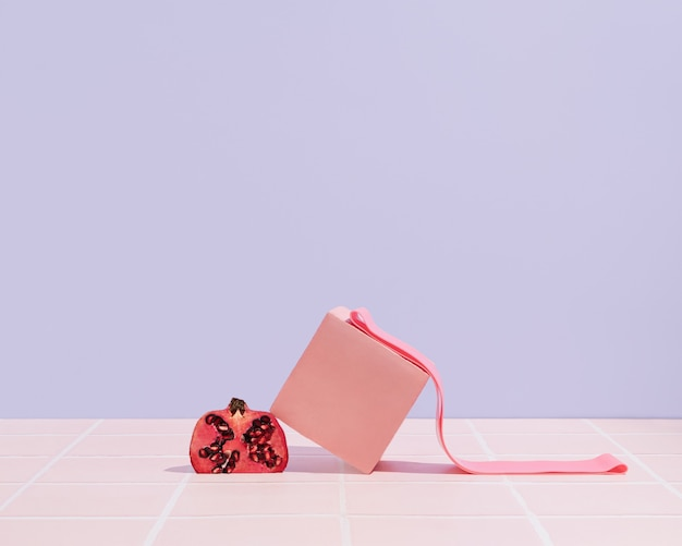 Rosa 3d-würfel, granatapfel und fitness-gummiband auf pastellviolettem hintergrund. trainingskonzept zu hause oder im fitnessstudio. gesunde lifestyle-szene. foto mit minimaler sportausrüstung.