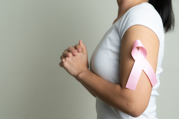 Rosa abzeichenband auf betendem frauenarm, um brustkrebsursache zu unterstützen.