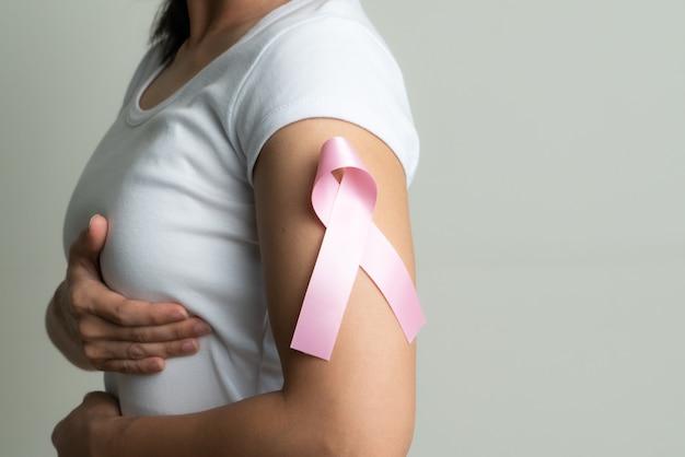 Rosa abzeichenband auf frauenarm, um brustkrebsursache zu unterstützen.
