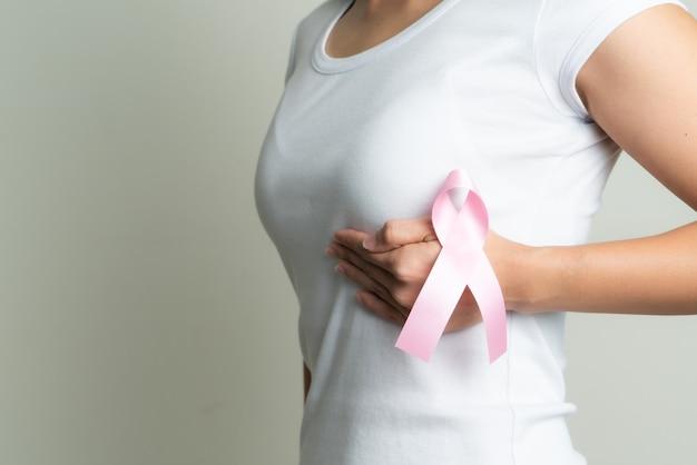 Rosa abzeichenband auf frauenhand, die brust berührt, um brustkrebsursache zu unterstützen. konzept zur aufklärung über brustkrebs