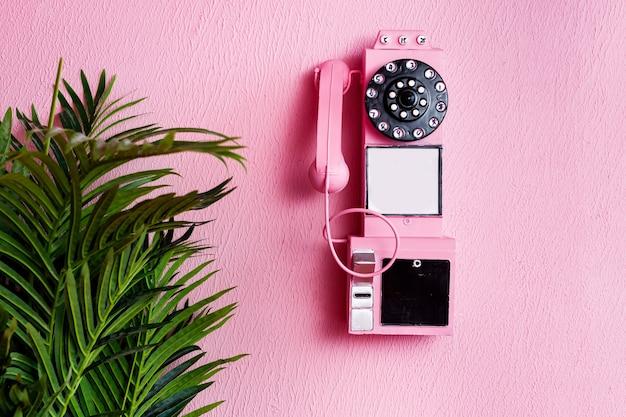Rosa altes traditionelles telefon mit empfänger auf pastellrosa hintergrund und grüner pflanze mit kopierraum