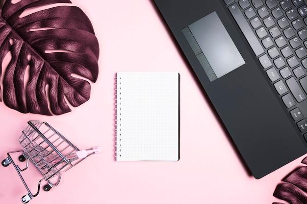 Rosa arbeitsbereich mit leerem notizbuch.
