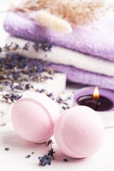 Rosa aromabadebomben in spa-zusammensetzung mit trockenen lavendelblüten und handtüchern. aromatherapie-arrangement, zen-stillleben mit brennenden kerzen