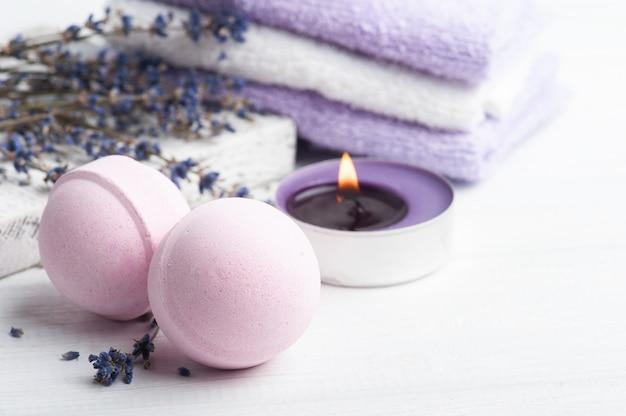 Rosa aromabadebomben in spa-zusammensetzung mit trockenen lavendelblüten und handtüchern. aromatherapie-arrangement, zen-stillleben mit brennender kerze