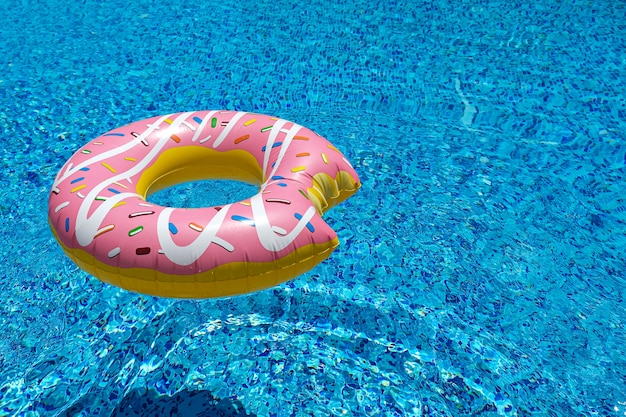 Rosa aufblasbare donut donut schwimmende matratze im schwimmbad. strandpoolzubehör. sommerferienkonzept.