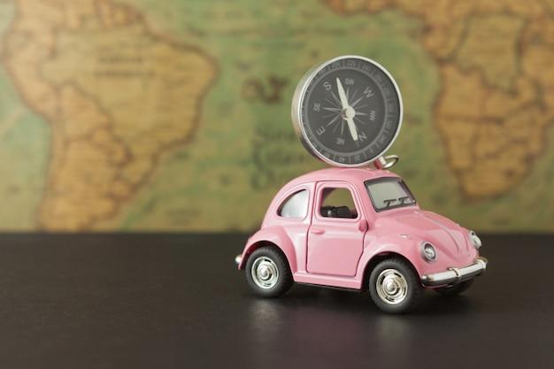 Rosa auto und kompass auf weinlesekarte