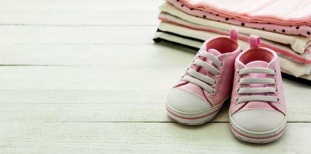 Rosa babyschuhe und neugeborene kleidung. mutterschafts-, bildungs- oder schwangerschaftskonzept mit kopierraum. baner.