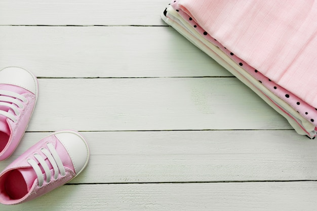 Rosa babyschuhe und neugeborene kleidung. mutterschafts-, bildungs- oder schwangerschaftskonzept mit kopierraum. flach liegen.