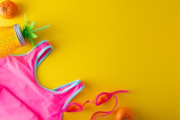 Rosa badeanzug und ananasglas für saft. sommerhintergrund mit exemplarplatz.