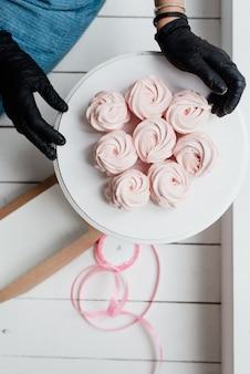 Rosa baiser auf einem weißen teller und händen eines konditoren in süßem essen der schwarzen handschuhe