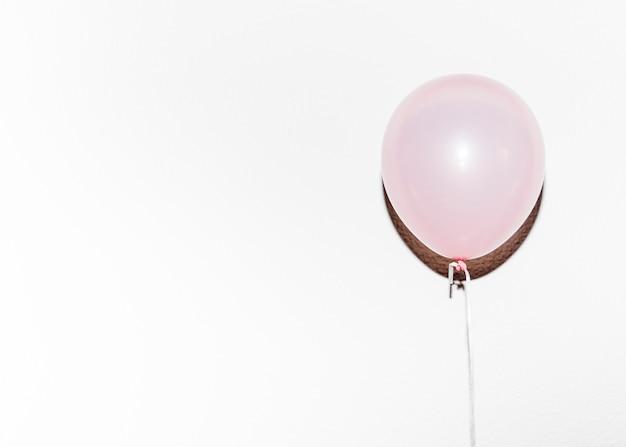 Rosa ballon des geburtstages mit schatten gegen weißen hintergrund