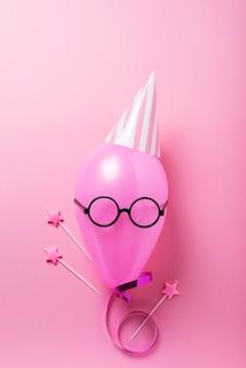 Rosa ballon mit partyhut und zauberstäben