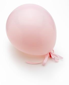 Rosa ballon mit zarten weißen schleifen. auf weißem hintergrund isoliert.