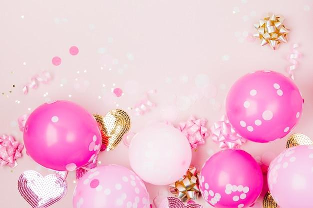 Rosa ballons mit konfetti, schleifen und papierdekorationen. geburtstagsfeier konzept thema. flache lage, ansicht von oben