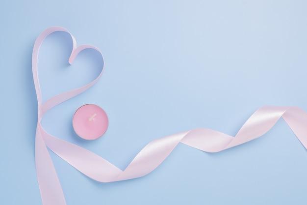 Rosa band in der form eines herzens und einer rosa kerze auf einem blauen hintergrund. platz für text. valentinstag konzept.
