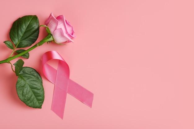 Rosa band und rose auf rosa hintergrund. brustkrebs-bewusstseinsmonatskonzept