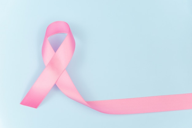 Rosa bandsymbol für brustkrebsbewusstseinskonzept auf blauem hintergrund