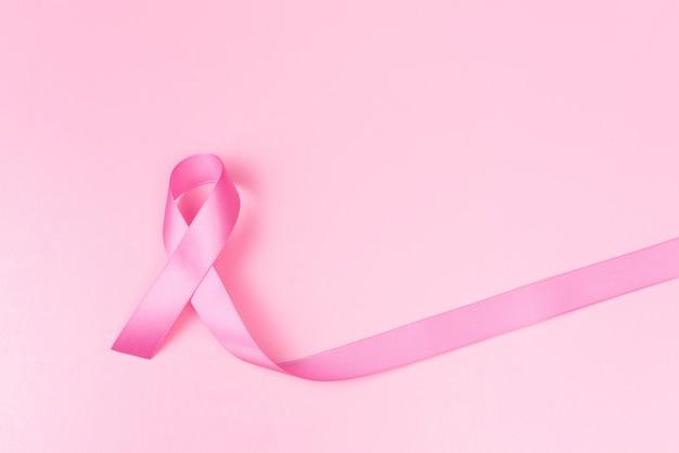 Rosa bandsymbol für brustkrebsbewusstseinskonzept über rosa hintergrund