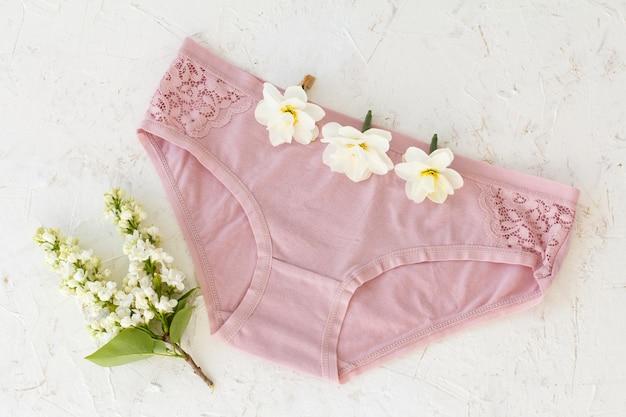 Rosa baumwollhöschen mit knospen von narzissenblüten und einem jasminzweig mit blumen auf weißem strukturiertem hintergrund. damenunterwäsche eingestellt. ansicht von oben.