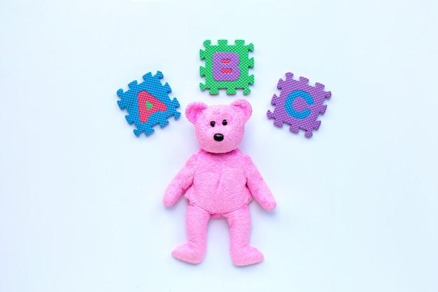 Rosa beartoy mit englischem alphabet-puzzle auf weißem hintergrund. bildungskonzept.