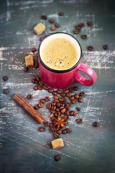 Rosa becher mit heißem kaffee und gewürzen auf schäbigem hintergrund