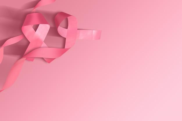 Rosa bewusstseinsband auf einem farbigen hintergrund