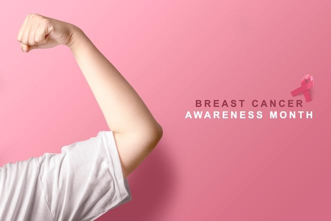 Rosa bewusstseinsband auf rosa hintergrund. brustkrebsbewusstsein