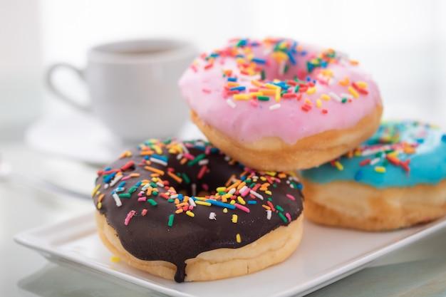 Rosa, blau und schokolade streuen donuts auf einen weißen teller und eine tasse kaffee