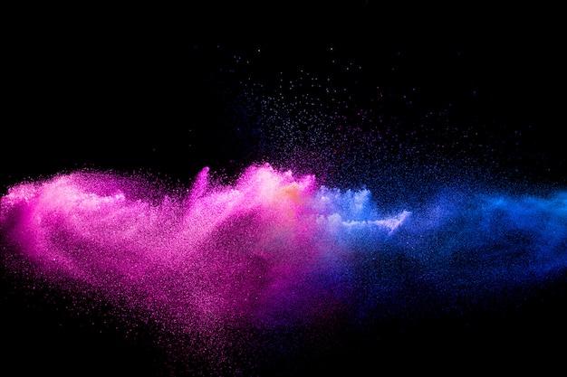 Rosa blaue staubpartikel spritzen auf schwarzem hintergrund.
