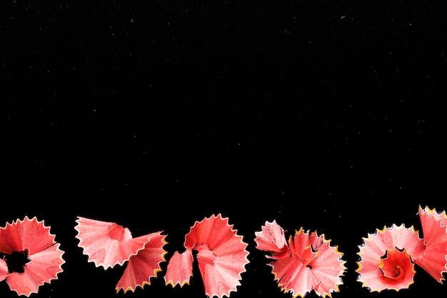 Rosa bleistiftschnitzel auf schwarzem schreibtisch