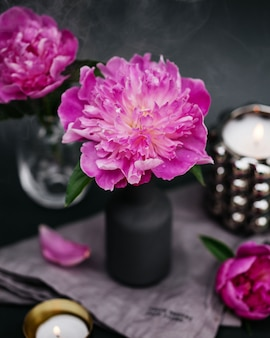 Rosa blühende pfingstrosenblütenknospe in einer grauen vase mit kerzen im lebensstil