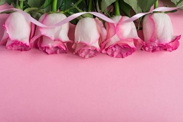 Rosa blühende rosen und band auf pastellrosahintergrund. romantischer blumenrahmen. kopieren sie platz