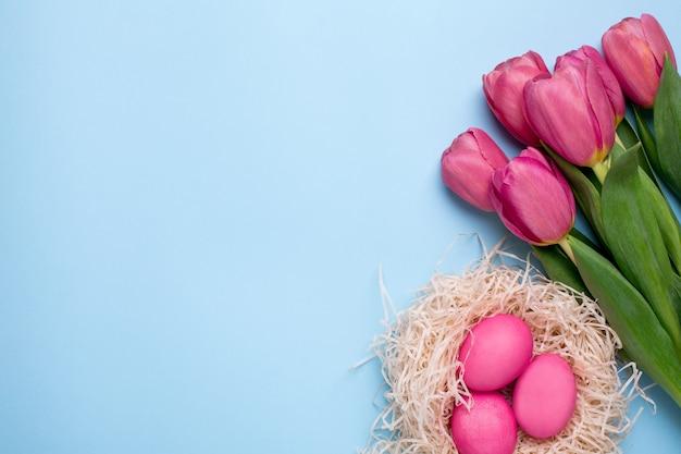 Rosa blüht tulpen mit ostereiern auf einer blauen oberfläche