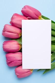 Rosa blüht tulpen und geschenkkarte auf einer blauen oberfläche