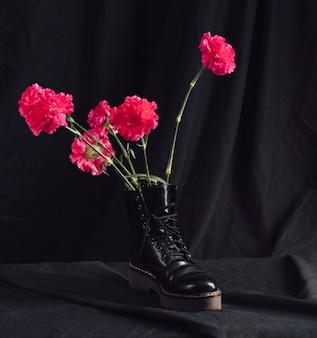 Rosa blüten im dunklen stiefel