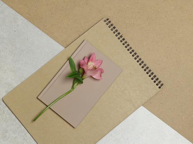 Rosa blume, handwerksalbum auf grauem und braunem hintergrund