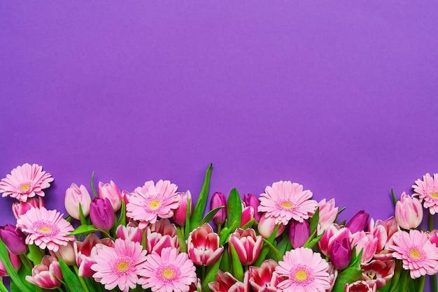 Rosa blumen auf violettem tisch. speicherplatz kopieren. feiertagstisch.
