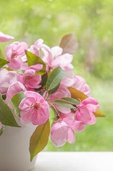 Rosa blumen des dekorativen apfelbaums in einer kleinen weißen vase auf einer fensterbank. bild für designpostkarten, kalender, buchumschlag. selektiver fokus.