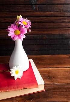 Rosa blumen im weißen vase auf buch