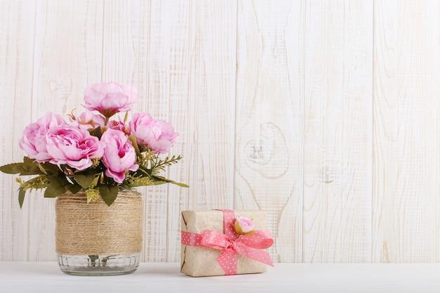 Rosa blumen in einem vase und in einem geschenk im kraftpapier auf dem tisch
