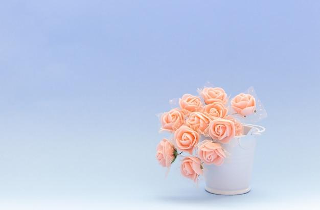 Rosa blumen in einem weißen spielzeugeimer auf einem blauen oder purpurroten hintergrund