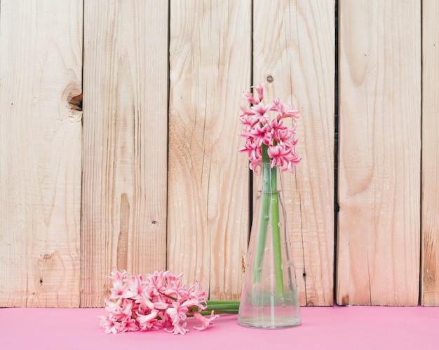 Rosa blumen in einer vase auf einem hölzernen hintergrund. rosa hintergrund