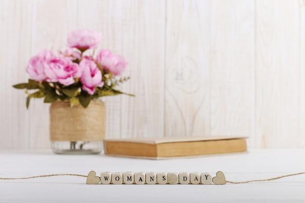 Rosa blumen in einer vase, ein buch liegen auf dem tisch