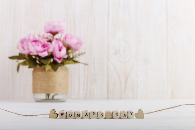 Rosa blumen in einer vase liegen auf dem tisch. perlen mit buchstaben, frauentag.
