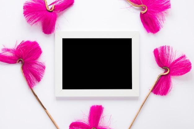 Rosa blumen mit leerem rahmen auf weißer tabelle