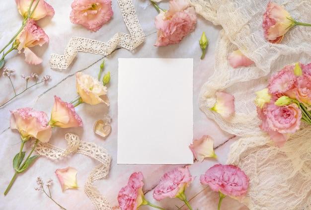 Rosa blumen und eine leere grußkarte, die auf einem marmortisch liegt, der mit vintage-bändern verziert ist?